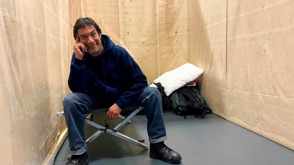 L'homme est assis sur un lit de camp avec des sacs poubelles posés par terre, un sac à dos et un oreiller.