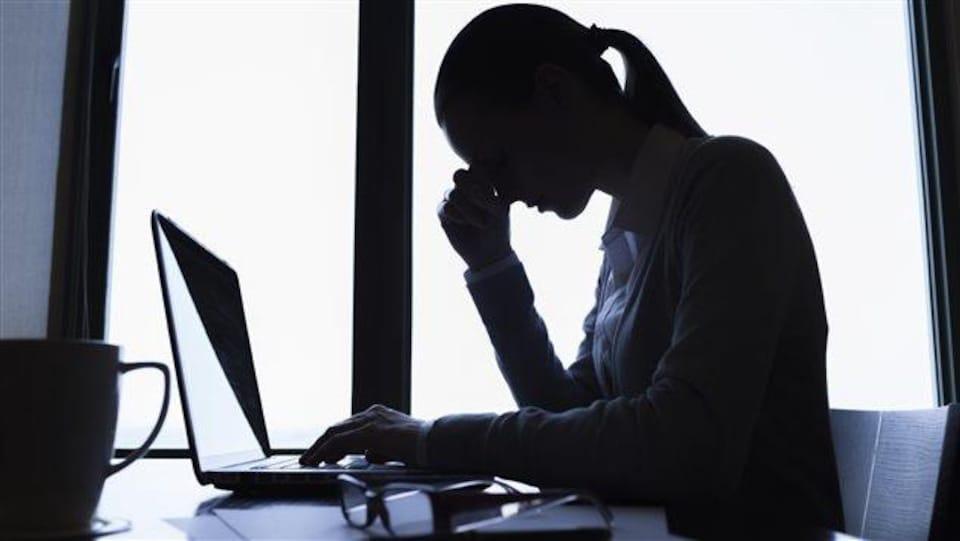 Une femme au travail semble fatigué et se tient la tête avec la main.