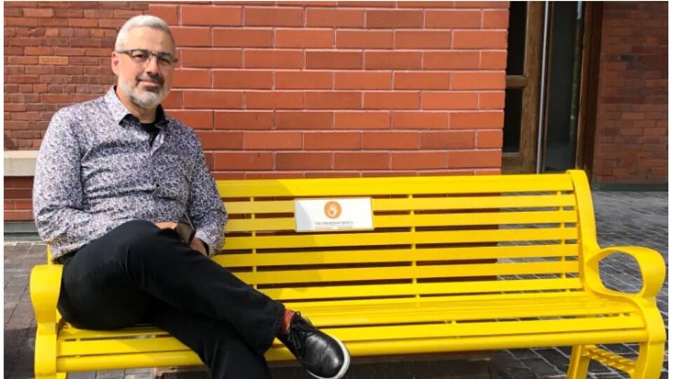 Un homme assis sur un banc jaune.