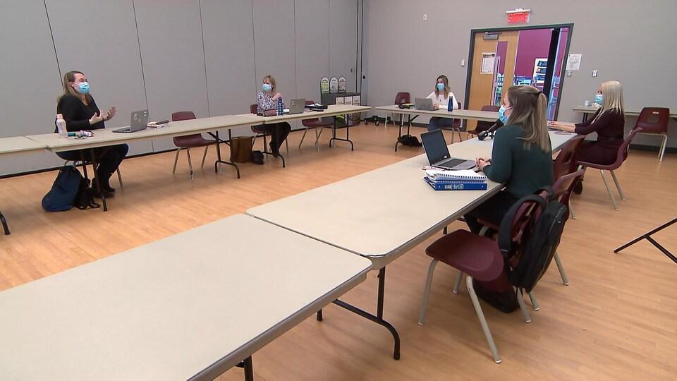 Cinq femmes discutent autour d'une grande table.