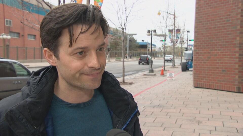 Un homme en entrevue devant la Maison du citoyen, à Gatineau.