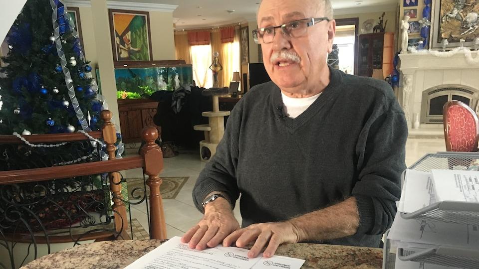 Santino Ianniciello assis à une table, avec des documents devant lui.
