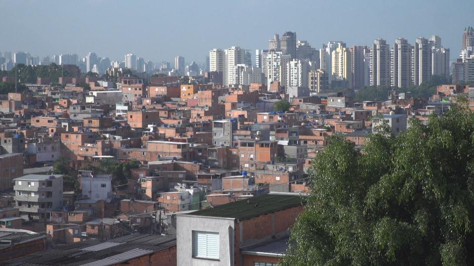Vue sur plusieurs petites maisons au pied de gratte-ciels plus imposants à Sao Paulo.