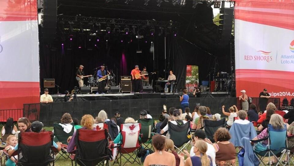 Une foule écoute les artistes qui jouent sur une scène extérieure