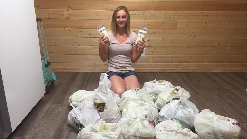 Une jeune femme à genoux avec un carton de lait maternel dans chaque main et plusieurs sacs de plastique pleins devant elle.