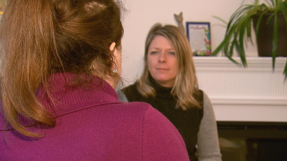 Une femme de dos, avec un chandail rose, et devant elle, une femme de face qui la regarde.