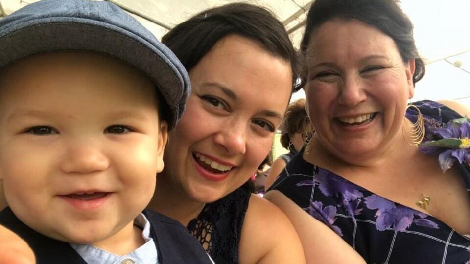 Trois générations de la mère famille posent, tout sourire.
