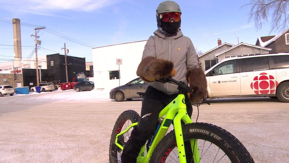 Une femme en vélo à pneus surdimensionnés, en habit de neige avec des gants en fourrure de castor.