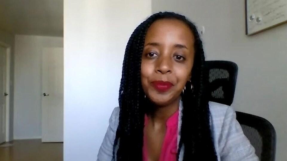 Une jeune femme, assise dans un bureau, en vidéoconférence.