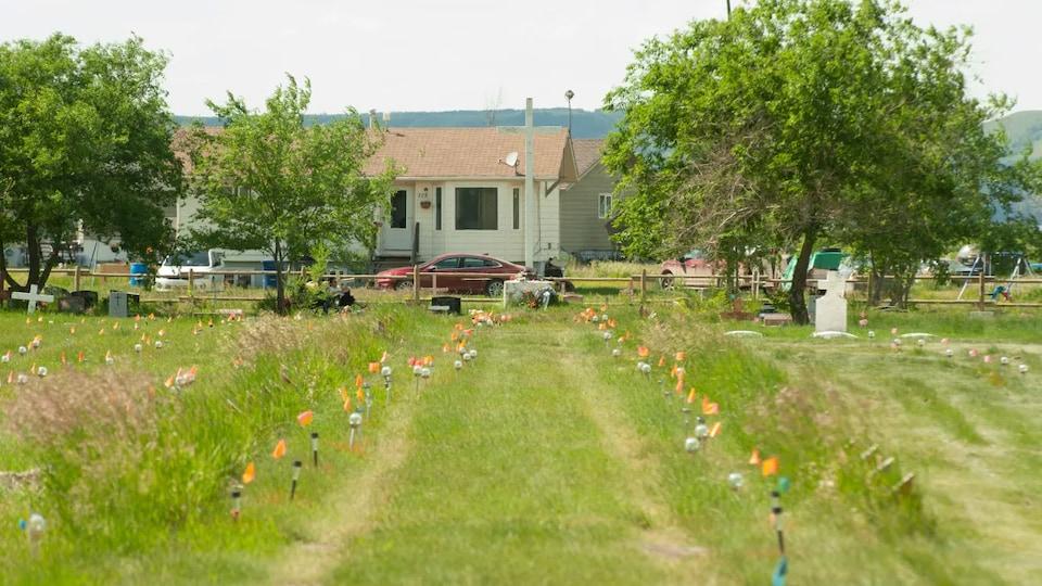 Petits drapeaux plantés dans le sol sur l'ancien terrain du pensionnat pour Autochtones de Marieval.
