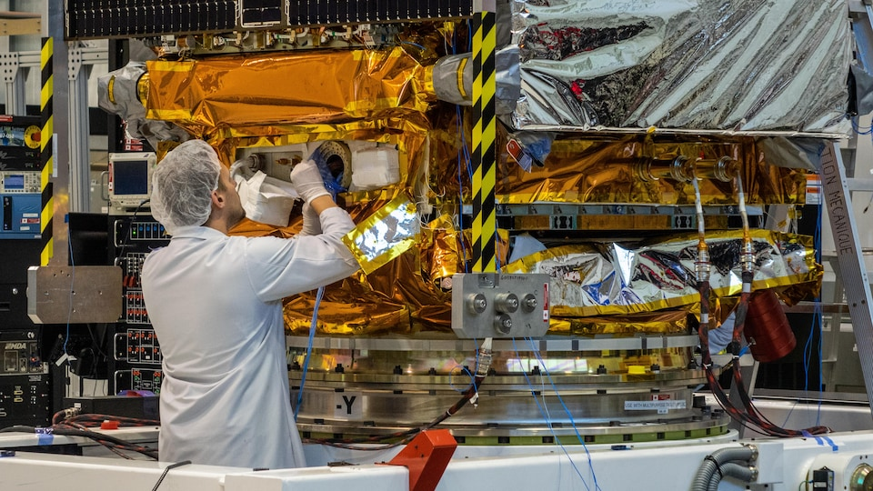 Une photo montre un ingénieur de l'entreprise MDA qui effectue des travaux sur l'un des trois satellites canadiens de la Constellation RADARSAT qui doivent être lancés cette semaine.