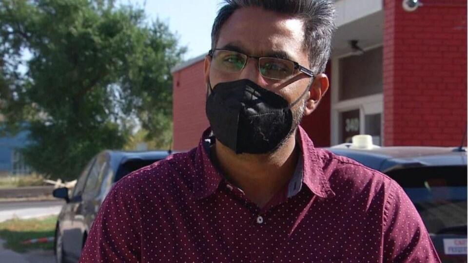 Satwinder Shahi porte une chemise rouge vin à pois. Il porte un masque noir. Il est photographié à l'extérieur devant une bâtisse en briques rouges.