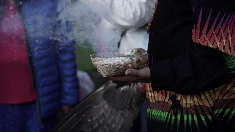 Un homme tient un bol duquel sort de la fumée