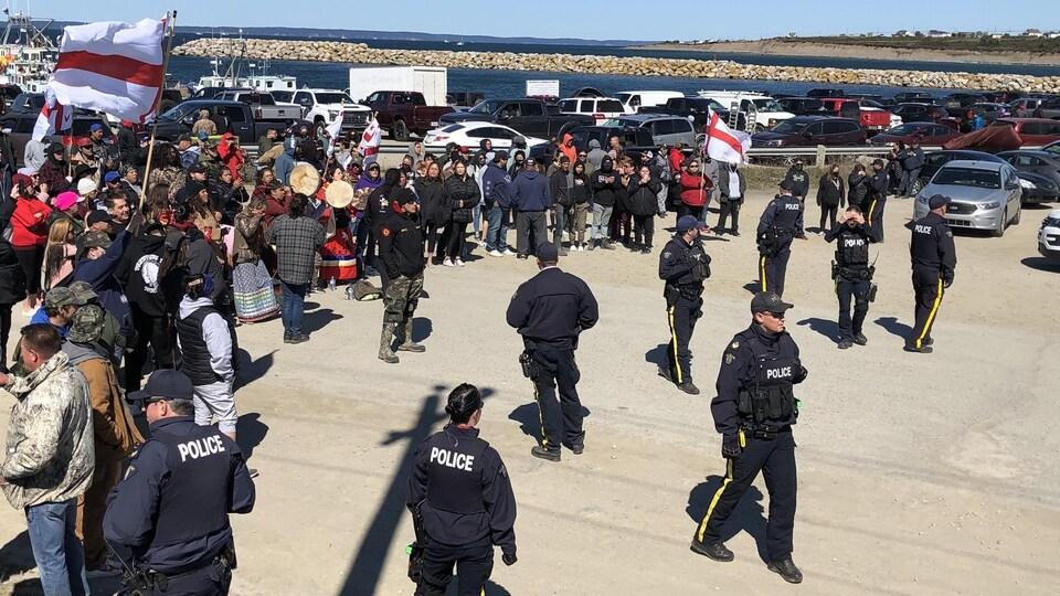 Un groupe d'Autochtones sur le quai, plusieurs tenant des drapeaux mi'kmaq, et des policiers devant pour s'interposer entre eux et un autre groupe.
