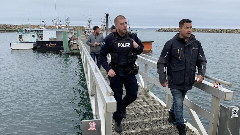 Deux policiers marchent sur un quai.