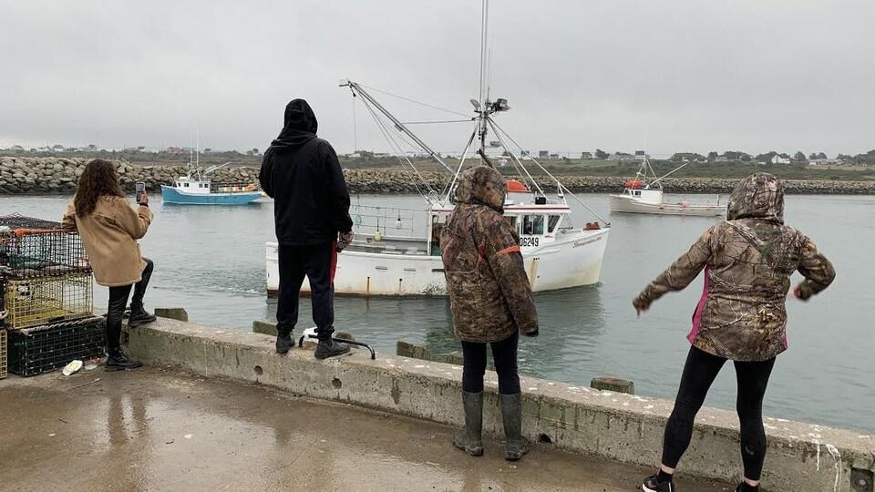 Quatre personnes sur le quai font des gestes en direction des pêcheurs.