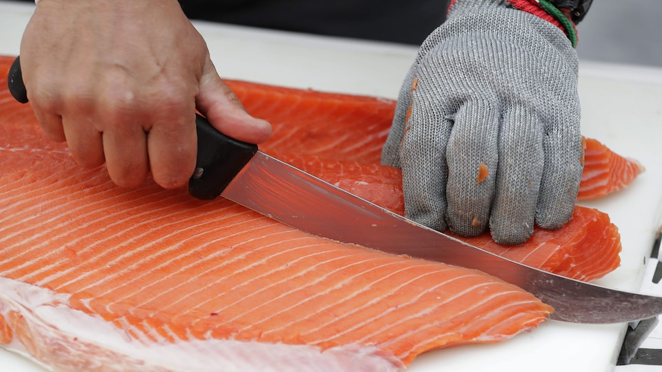 Un poissonnier tranche un morceau de saumon.