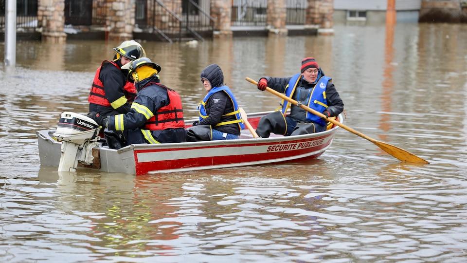 Des pompiers dans une chaloupe sauvent des citoyens, alors que la rue est inondée.