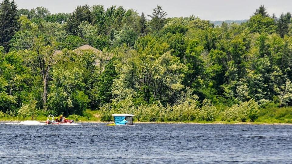 Un bateau de secours s'approche d'une embarcation renversée.
