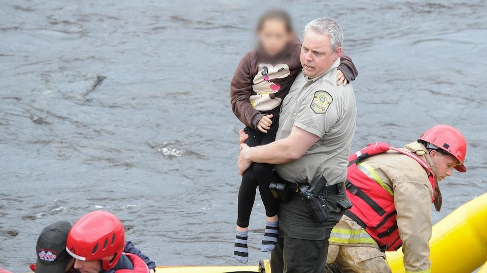L'agent Éric Bernard avec la fillette de 10 ans qu'il a sauvé de la noyade.