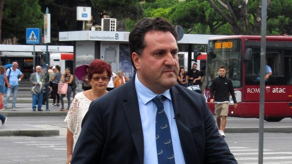 On voit Saverio de Bonis en train de marcher dans une rue de Rome, en Italie.