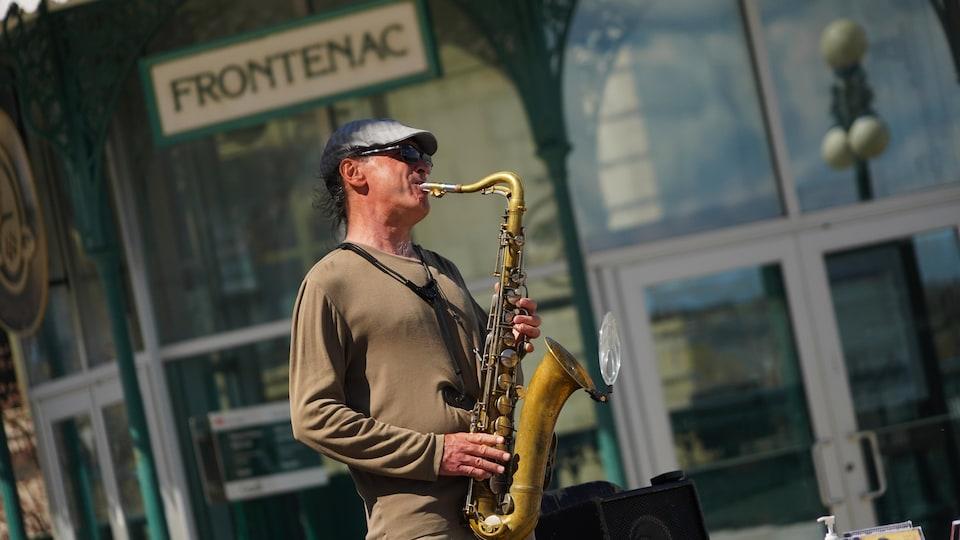 Un musicien joue du saxophone sur la Terrasse Dufferin.