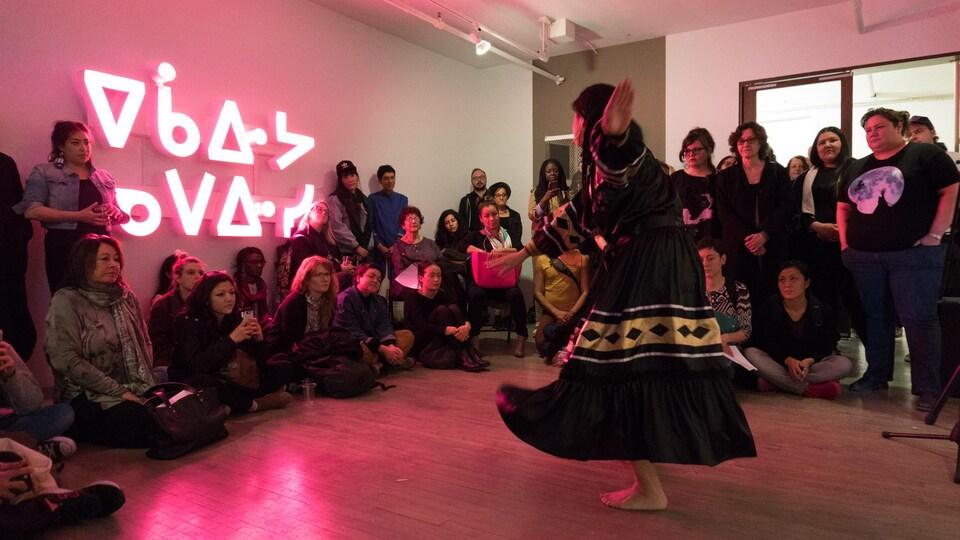 Des gens regardent une femme habillée de vêtements autochtones qui danse.