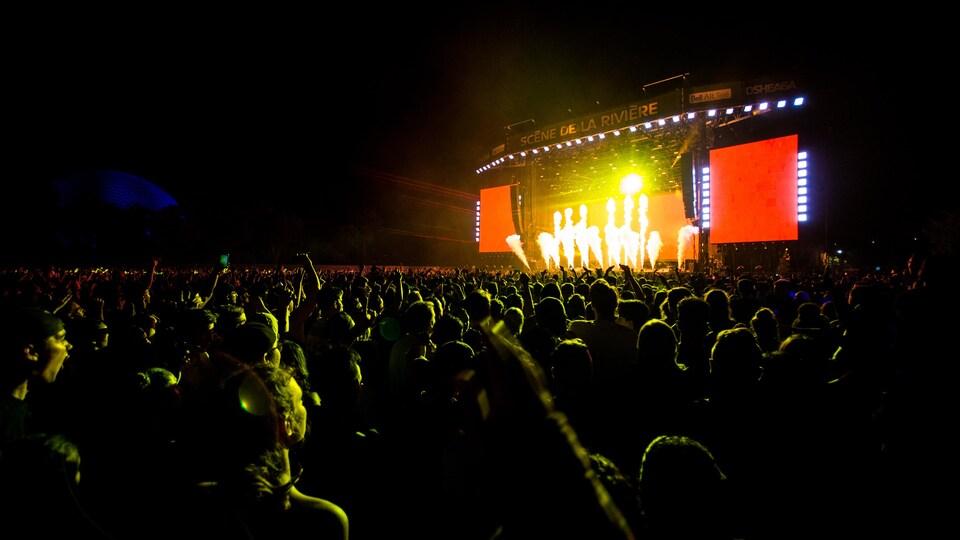 La scène de la Rivière est illuminée; des milliers de personnes regardent le spectacle.