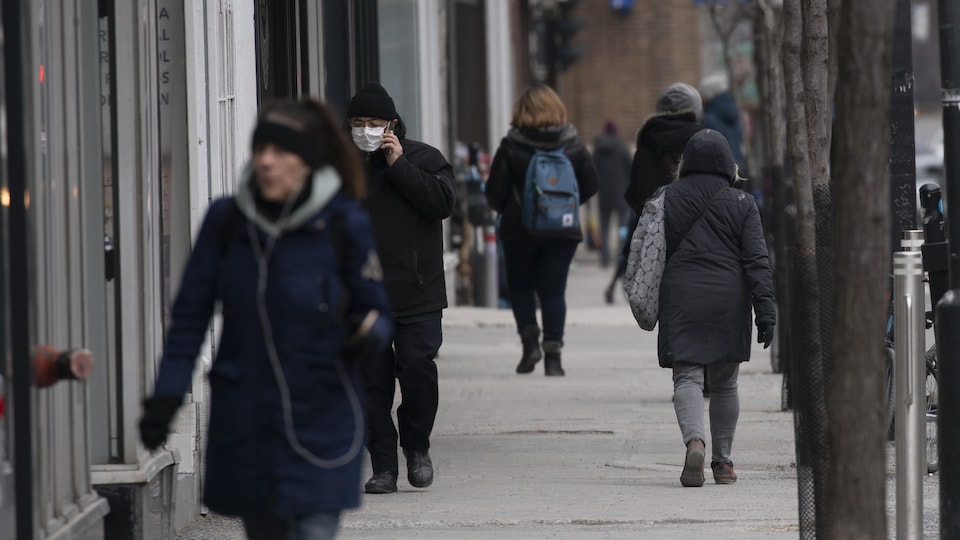 Plusieurs personnes, dont une porte un masque, marchent sur un trottoir.