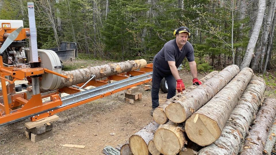 Un tronc d'arbre est posé sur la scierie pendant qu'André Frenette en dépose un autre sur un tas de billots.