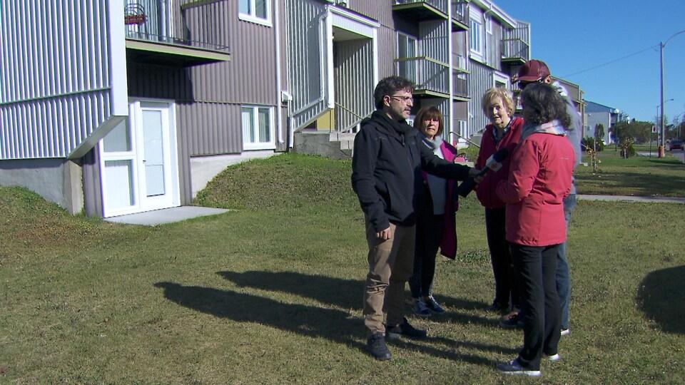 Un groupe de résidents témoigne au journaliste de leurs observations.