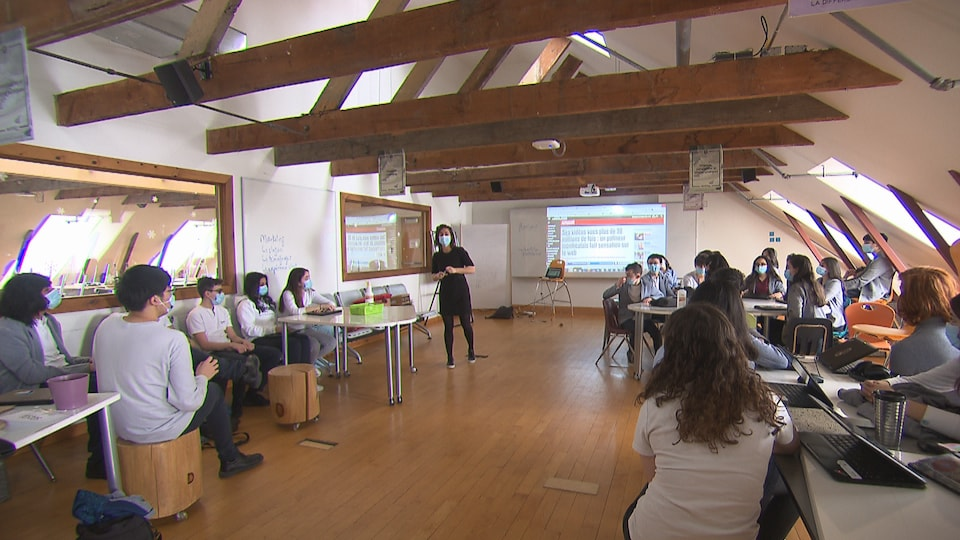 Des élèves sont assis et écoutent un professeur.