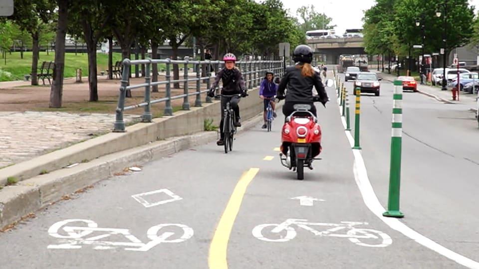 Une dame circule à scooter électrique sur une piste cyclable de Montréal. Elle croise des vélos.