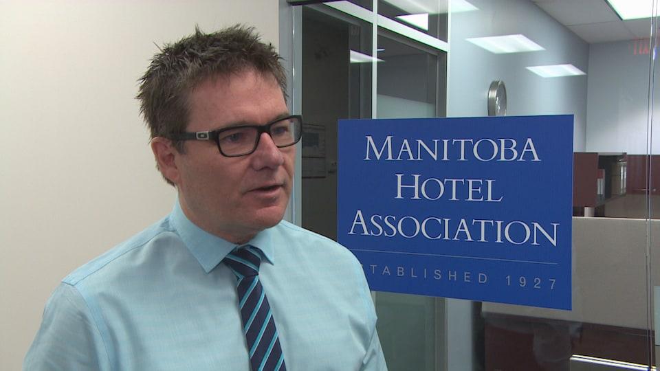 Un homme debout, et derrière lui une affiche indiquant : Manitoba Hotel Association.