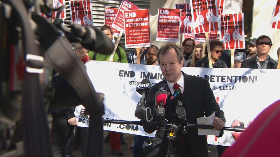Le conseiller parle lors d'un point de presse devant des manifestants