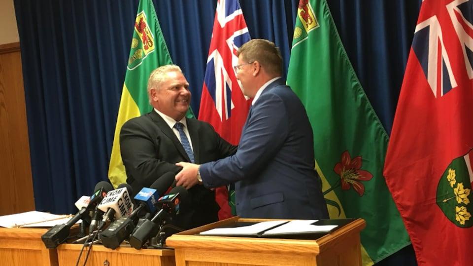 Scott Moe et Doug Ford se serrent la main devant les drapeaux provinciaux