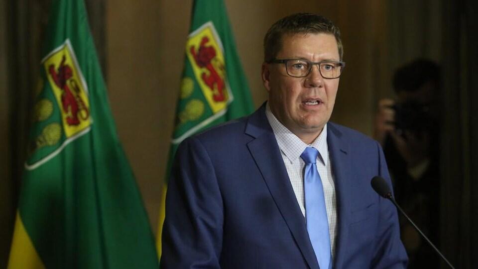 Scott Moe, le premier ministre de la Saskatchewan, parle devant un microphone en portant un costume-cravate et des lunettes.