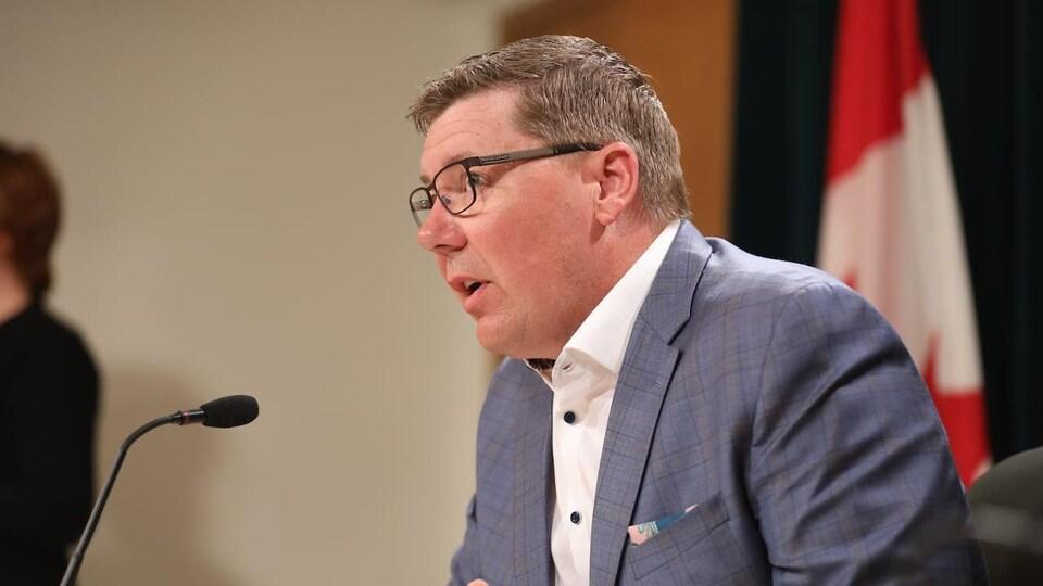 Le premier ministre de la Saskatchewan Scott Moe parle dans un micro lors d'une conférence de presse avec le drapeau canadien se situe derrière lui.
