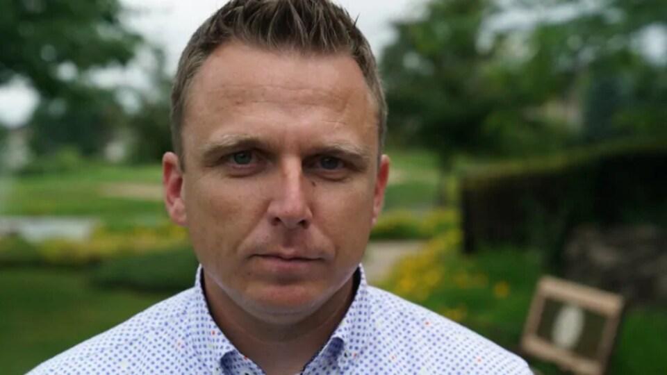 Scott Moffatt pose pour la caméra à l'extérieur pendant l'été.
