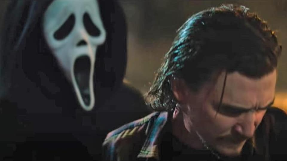 Un tueur portant un masque se tient derrière un homme qui regarde dans l'intérieur d'une voiture.