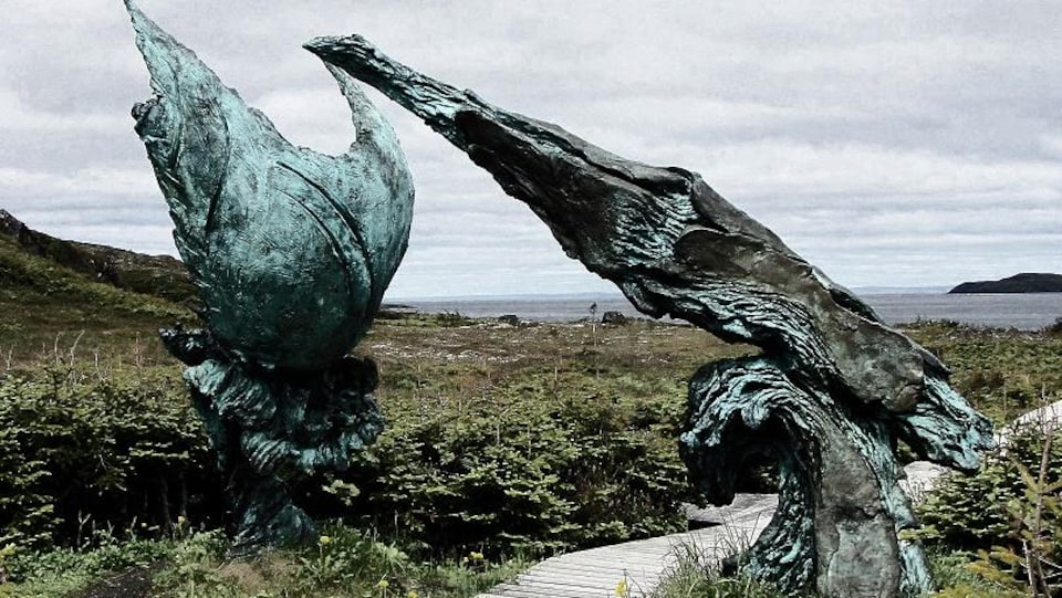 Une sculpture en bronze sur le bord de la mer.