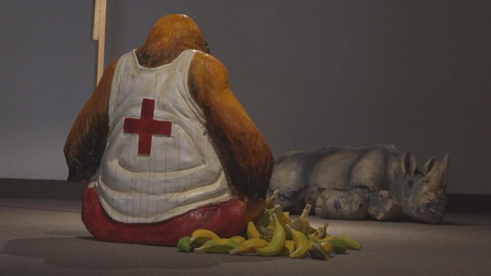 Un singe en tenue de sauveteur. Il est entouré de bananes. Un rhinocéros couché en arrière-plan.