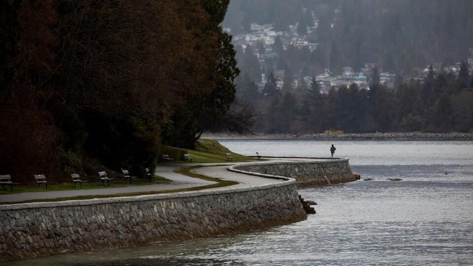 Une femme seule sur le sentier Seawall qui borde la mer, à Vancouver.
