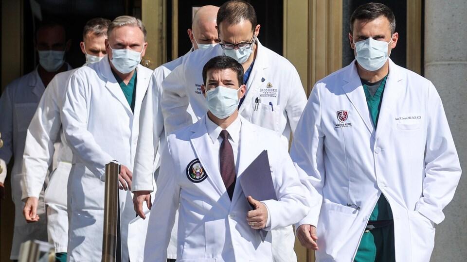 Une équipe de médecins en sarrau s'avance vers les journalistes.