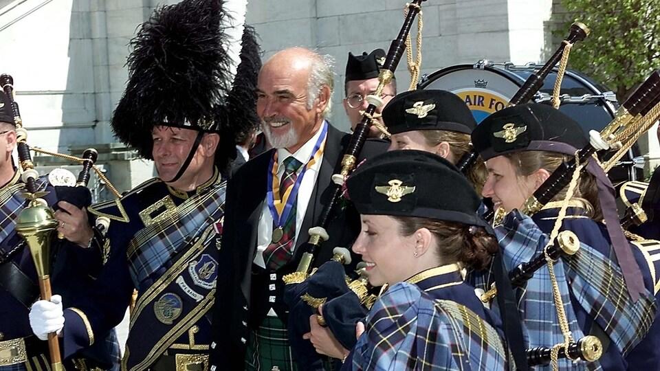 Sean Connery en kilt entouré de plusieurs personnes portant elles aussi le costumes traditionnel écossais.