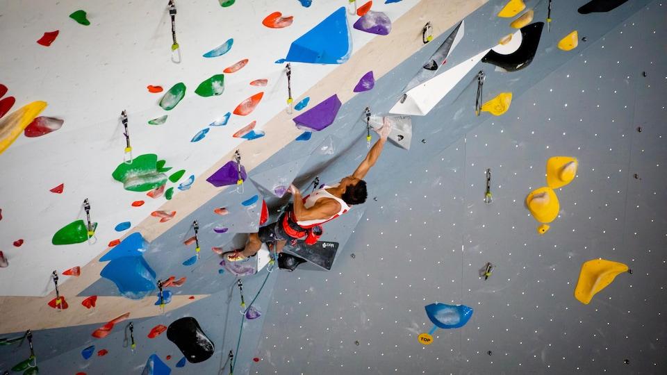 Sean McColl grimpe un mur d'escalade intérieur.
