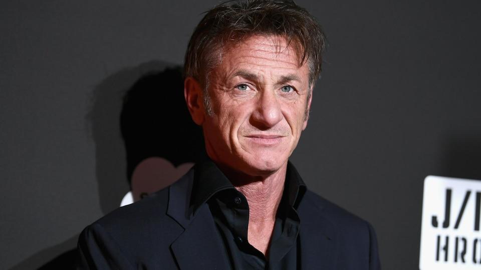 L'homme pose en chemise noire sur un fond noir.