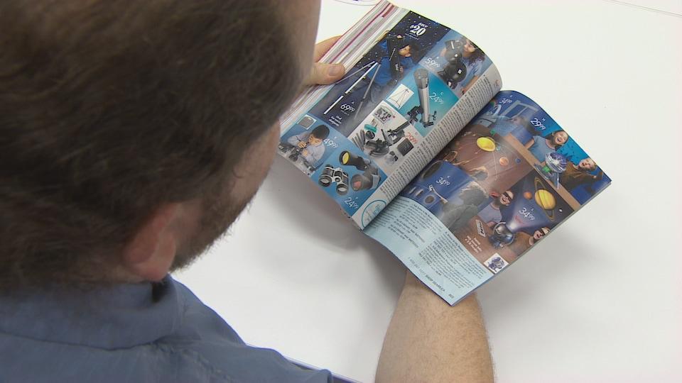 Un homme tourne les pages d'un catalogue.