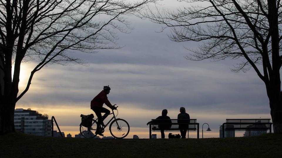 Un cycliste et des gens assis sur un banc dans un parc de Vancouver au coucher du soleil.