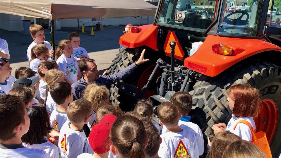 Près d'un tracteur, Sébastien Gaudreault discute avec des écoliers.